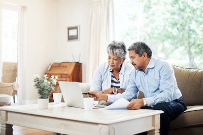 Older Couple Sitting on Couch Looking at Laptop